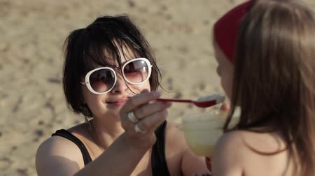 gruel : Close-up of young woman feeding little daughter on the beach