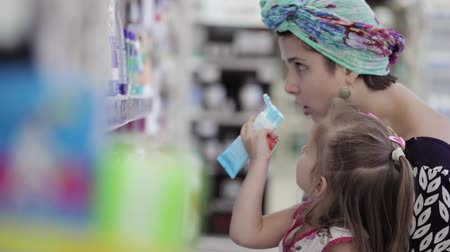 şampuan : Young woman with daughter buying body care products in supermarket