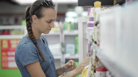 cheirando : Housewife choosing body care products in supermarket.