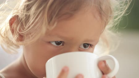 çay fincanı : Close-up portrait of beautiful little girl with a cup of tea Stok Video
