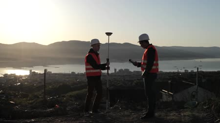 kurmak : Two surveyor in helmets performing geodesic measurements on top of the mountain