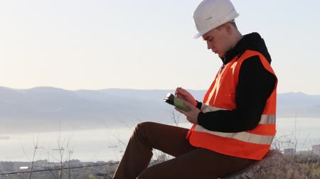 levelling : Handsome male engineer in vest and helmet sitting at his outdoor workplace