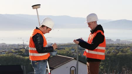 levelling : Two surveyor on the top of the mountain with town and sea background