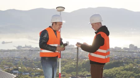 levelling : Workers in helmet performing geodesic measurements on the top of the mountain. Stock Footage