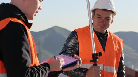 levelling : Surveyors performing geodesic measurements and fixing them to paper Stock Footage