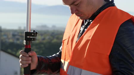 levelling : Surveyor performing geodesic measurements on he top of the mountain Stock Footage