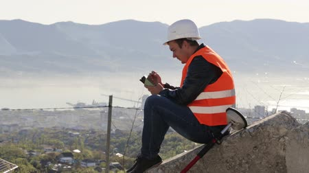 levelling : Caucasian worker in vest and helmet sitting on the concrete plates