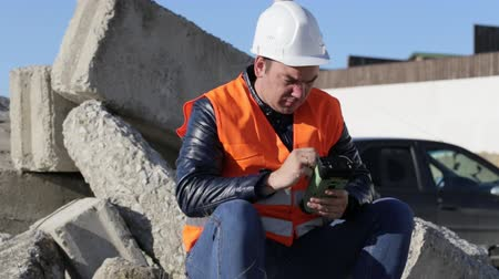 kurmak : Builder in vest and helmet sitting outdoor and working with geodetic device