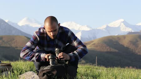 coffer : Photographer sitting and changing lenses on professional camera outdoor.