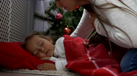 hora de dormir : Cute little girl in white sweater sleeping under Christmas tree at morning. Mother comes and covers baby with a red plaid. Than mom kissing daughter and going away.