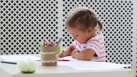 preschool : Cute preschool girl sitting by the white table and drawing something by pencil
