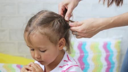 braid hairs : Young woman making plaits on her daughter hair