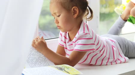little finger : Close up portrait of little cute girl reading book on windowsill at home.