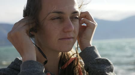 kulaklar : Closeup portrait of fitness woman putting on sport in-ear wireless headphones at the beach. Stok Video