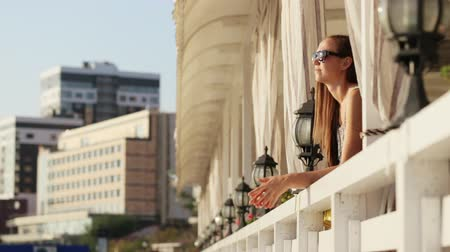 созерцать : Young pretty woman in dress and sunglasses goes to terrace of reataurant and beholding of beautiful view