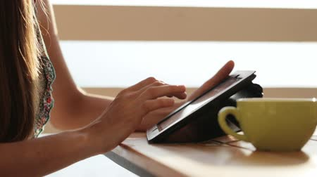 drží se za ruce : Close-up female hands using tablet in open air cafe. Woman in restaurant with tablet, hot beverage, fruits and croissant in warm sunrise light.