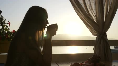 созерцать : Silhouette of young beautiful woman sits in a cafe with panoramic views of sea bay and drinking tea or coffee, profile view with beautiful sunrise light.
