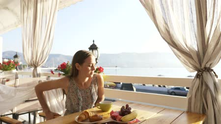 созерцать : Young pretty woman in dress sits in a cafe beholding beautiful panoramic views of sea bay. Morning with warm sunrise light and cup of coffee or tea Стоковые видеозаписи