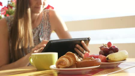 kruvasan : Close-up female hands using tablet in open air cafe. Woman in restaurant with tablet, hot beverage, fruits and croissant in warm sunrise light.