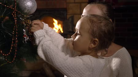 вешать : Young mother with little cute daughter decorating Christmas tree at dark living room with flaming fireplace on the background, 4k slow motion