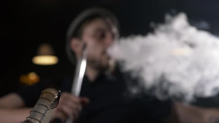 cimborák : Handsome young stylish men in hat smoking shisha at dark cafe. Camera focus moving from hookah on foreground to male on the background, slow motion 4K Stock mozgókép