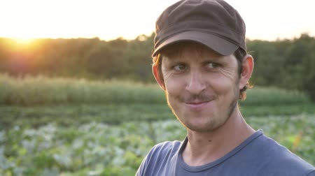 magány : Portrait of young cheerful farmer standing at field of organic farm, eating fresh ripe cucumber and smiling, 4k slow motion.
