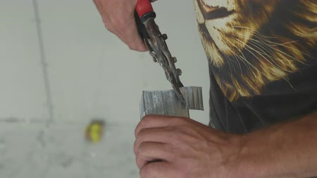locksmith : Hands of men cutting frame for mount drywall in unfinished apartments, close-up