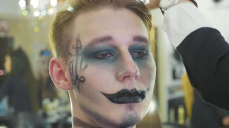 маскарад : Artist applying halloween makeup on male models face at beauty salon in slow motion.
