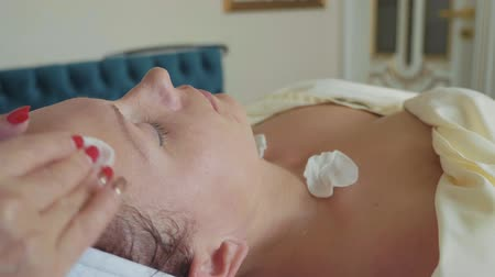 aydınlatmak : Professional cosmetologist is cleaning womans face using cotton sponge at luxury spa salon. Young woman is lying with closed eyes and enjoying cosmetic procedure with facial massage, slow motion