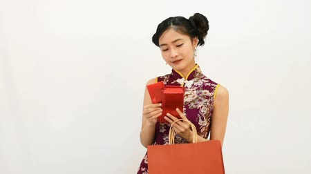 ano novo chinês : Young Asian beauty woman wearing cheongsam and finding red packet of money in her shopping bag for Chinese new year festival event on white background. Holiday and Lifestyle concept. Qipao clothes Vídeos