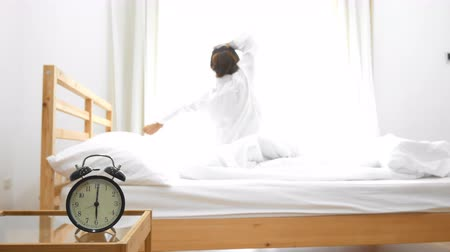 ébresztő óra : Woman getting up in morning with black alarm clock on front. Wake up time and Relaxing concept. Bedroom and Beauty theme. Stock mozgókép