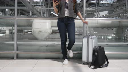 travel theme : Close up woman using smart phone and waiting for take off flight with luggage and baggage at airport. People and lifestyles concept. Technology and trravel theme.