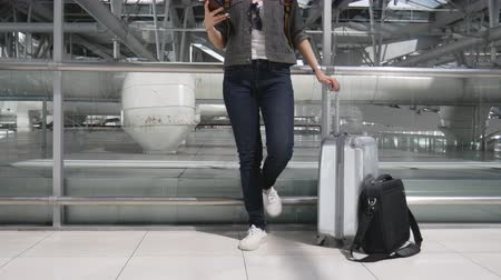 Close up woman using smart phone and waiting for take off flight with luggage and baggage at airport. People and lifestyles concept. Technology and trravel theme.