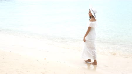travel theme : Beauty Asian woman walking along the beach. People and lifestyle concept. Summer vacation and relaxation theme. Happy life of woman footage. Stock Footage