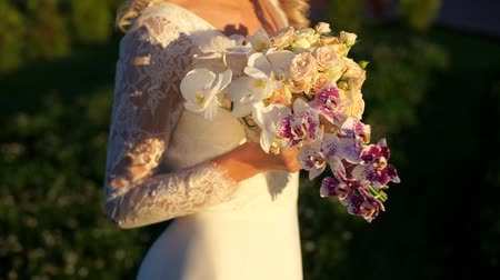 gentleness : The bride touches with his hands a bouquet of roses and orchids in the bright rays of the setting sun.