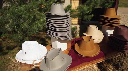 western wear : Cowboy hats are lined on the table.