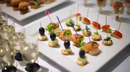 placas : Catering. Decorated table, kanape salmon sprinkled with sesame seeds, stuffed with cheese.