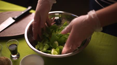 healthyfood : Salad leaves with sesame seeds. Man stirs the salad with his hands.