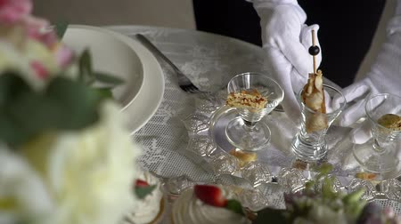 consist : A waiter in white gloves straightens a snack on a silver tray.