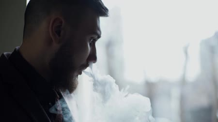 oblek : close-up of a bearded man in suit smoking electronic cigarette