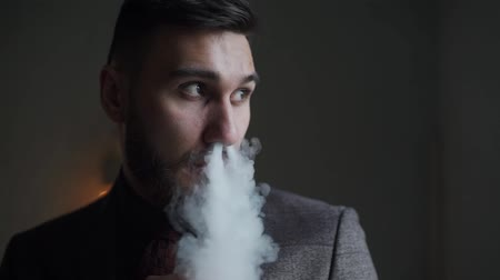 борода : close-up of a bearded man in suit smoking electronic cigarette