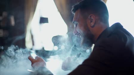 planları : Modern hipster businessman drinking coffee in cafeand working on tablet smoking e-cigarette vape Stok Video