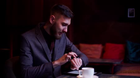 hoşlanmak : Casual businessman reading on tablet pc at the cafe