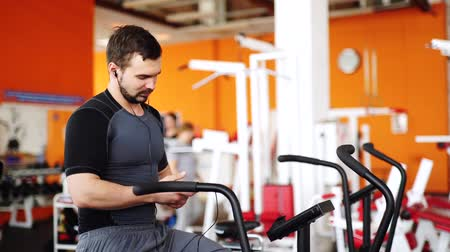 tek başına : Man listen to music and riding stationary bike in the gym taking selfie Stok Video