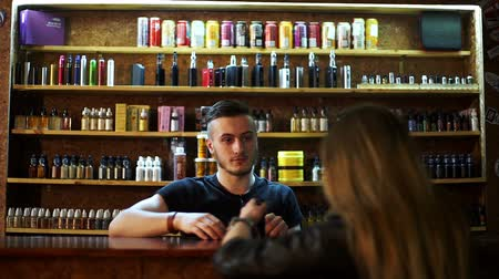 kirakat : seller in vape shop shows to young girl e-cigarettes and showing how it works Stock mozgókép