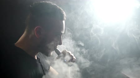 kirakat : young vaper man exhaling big clouds of smoke with e-cigarette vape in slowmotion