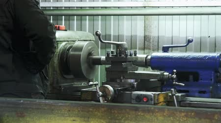 karbantartás : Turning lathe in action.Facing operation of a metal blank on turning machine with cutting tool.Old turning lathe machine in turning workshop.Operator machining high precision mold part by cnc lathe Stock mozgókép