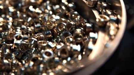 flange : Small parts, balls spinning and revolve, rotate in the tray blanks. Will soon begin their treatment. Punching small parts on automatic lathe Stock Footage