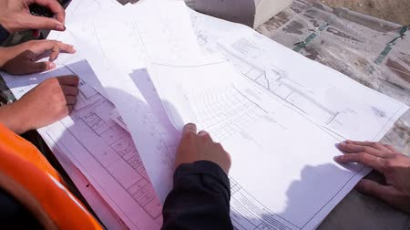 инспектор : Building plan lying on the bricks. Engineers and construction workers studying drawing. Close-up