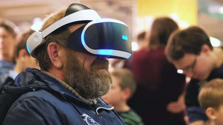 January 2018 - Virtual Reality Headset - Father trying out the new technology. The old man is trying new technologies. Trying virtual reality glasses